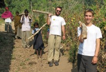 Students helping villagers carry logs