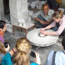 Student trying a hand at the pottery wheel during a workshop